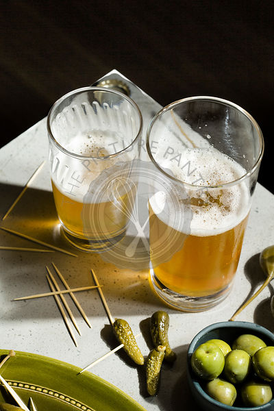 Beer and snacks. A selection of pickled gherkins, caper berries and green olives accompany two glasses of beer on a concrete ...