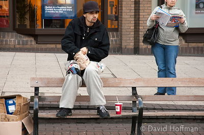Young man eating his breakfast outside Angel tube station, Islington, London.