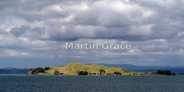 2:1 format image of the well-preserved volcanic Browns Island (Motukorea) in evening sunlight with a threatening sky, Hauraki...