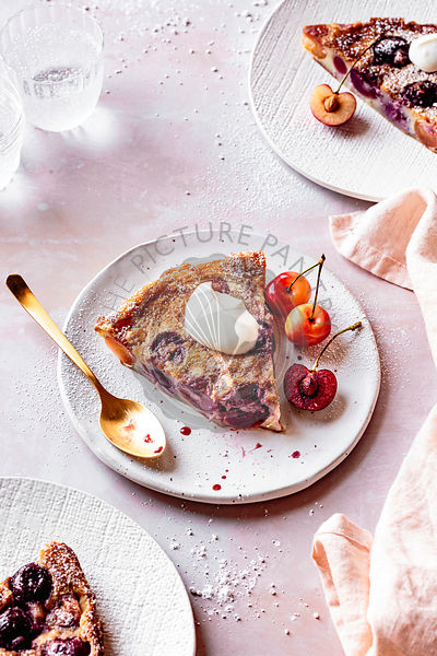 A slice of cherry clafoutis served with fresh cherries and creme fraiche.