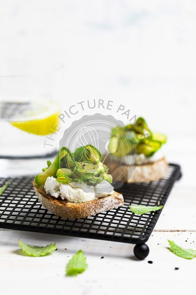 Toast with ricotta and marinated zucchini on a rack on a white wooden board
