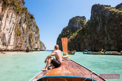 Mature man relaxing on boat prow, Phi Phi island, Thailand