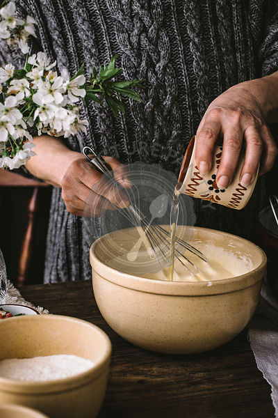 A woman cooking a bundt cake at home in a rustic kitchen, on a wooden table.
