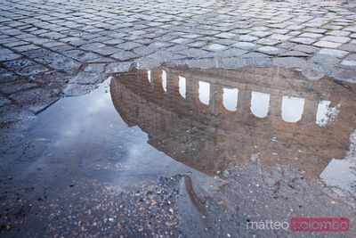 Colosseum reflected in puddle, Rome, Italy