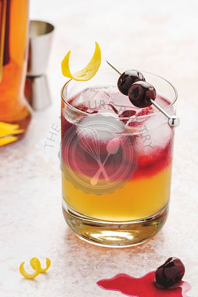 New York Whiskey sour in a glass with ice cubes, cherries on top with syrup and lemon zest garnishes.