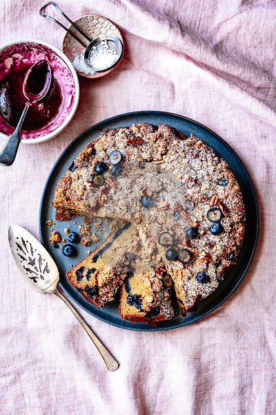 Blueberry coffee cake with pecan streusel dusted with icing powder on a ceramic plate.