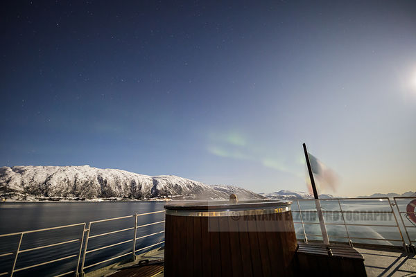 Tourist enjoying the hot tub on the rear deck of the Polarfront while the northern lights start dancing in the sky, Tromso, N...
