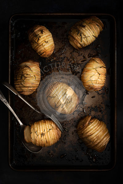 Roasted hasselback potatoes on a baking tray.