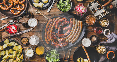 Flat-lay of Bavarian Octoberfest dinner with beers, sausages and snacks