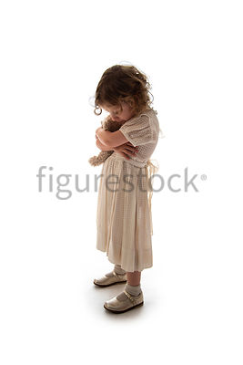 A litle girl in a dress clutching a teddy bear – shot from mid level.