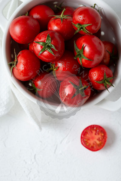 Freshly washed cherry tomatoes in a white colander. Overhead view.