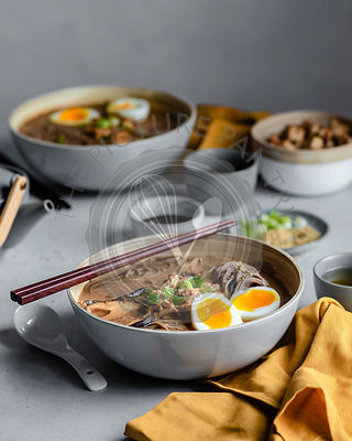 A bowl of miso soup, garnished with green onions and soft boiled eggs, with a pair of dark wood chopsticks balanced atop the ...