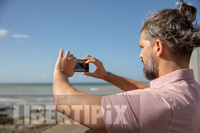 GAY MAN TAKING PHOTOGRAPHS, OF THE SEA, ON A CAMERA PHONE