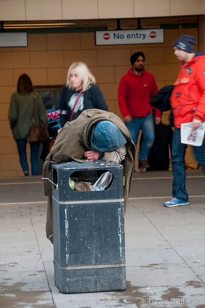 Homeless man searching rubbish bin for food.
