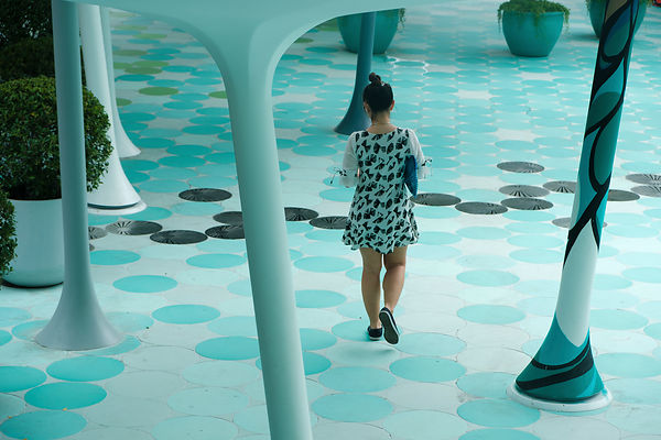 A rear view of walking girl in a patterned clothe very similar to pattern of the floor. Siam Square. Bangkok. Thailand