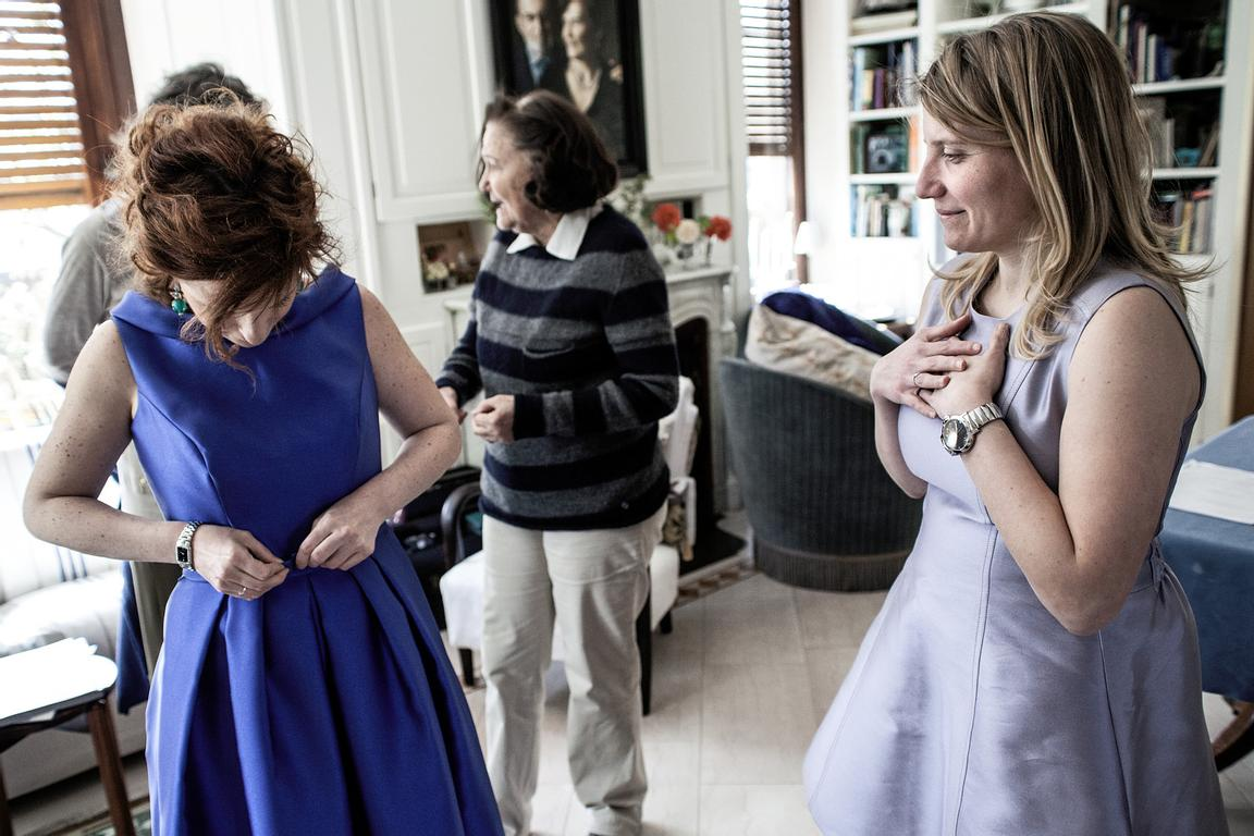 Giulia (l) and Mari (r) trying their wedding dresses on at Giulia's mother's (c) home in order to help the floral designer to...