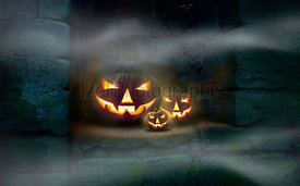 Three Jack O' Lanterns on a stone cut out in the ruins of an old monastery with mist in the air.
