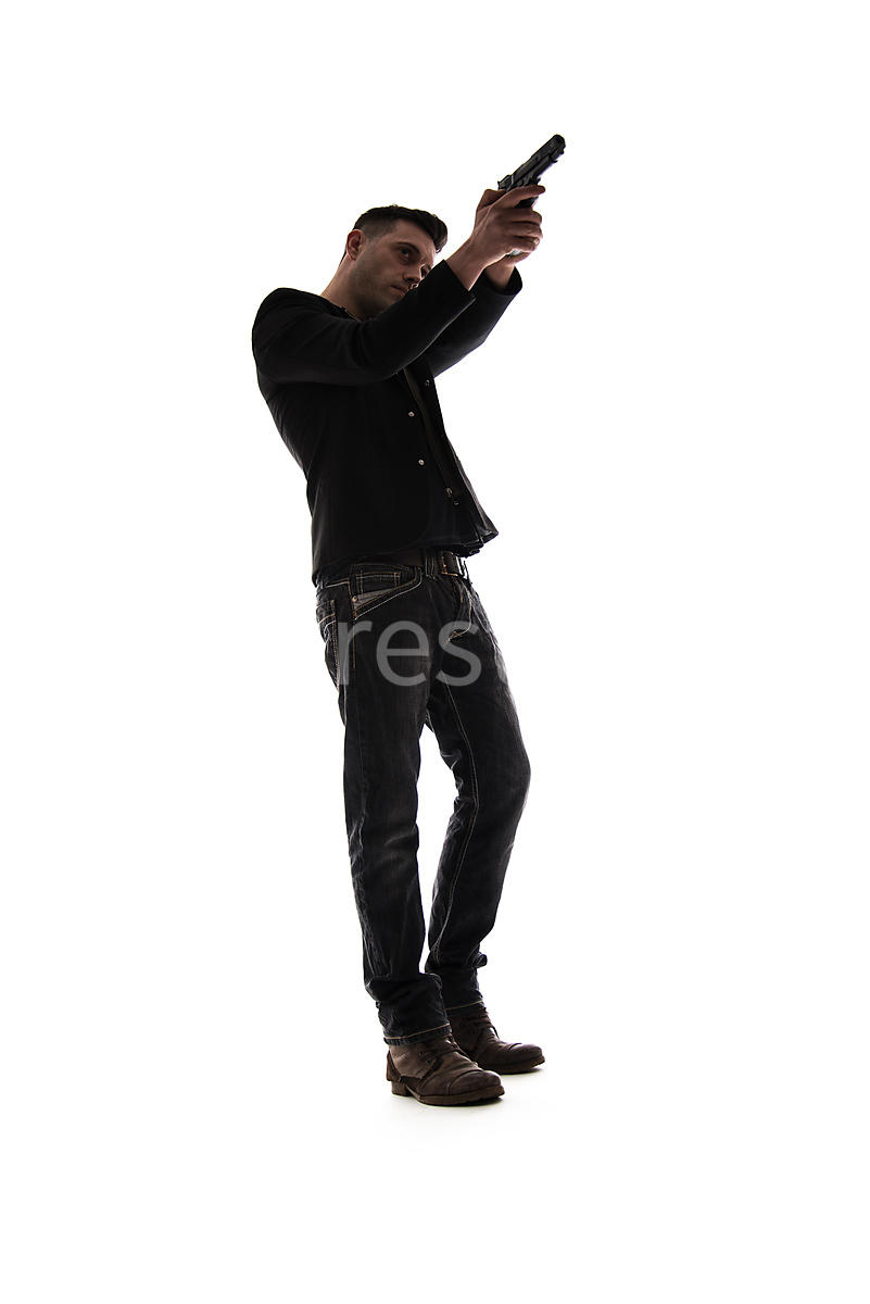 A Figurestock image of a man pointing a gun, in semi-silhouette – shot from low level.