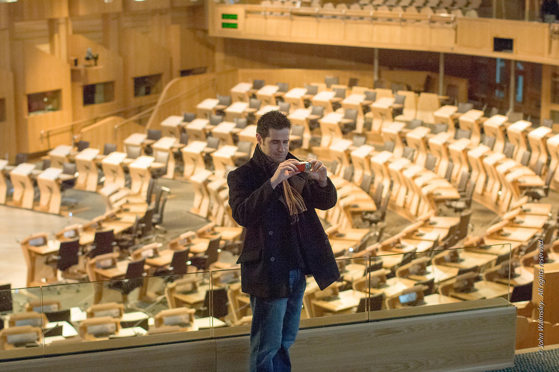#027693,  Visitor taking photos in the debating chamber at the new Scottish Parliament building at Holyrood, Edinburgh.  Desi...
