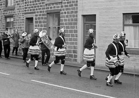 #77106,  The 'Nutters' Dance', Bacup, Lancashire,  1973.  On Easter Saturday every year the 'Coconut Dancers' gather at one b...