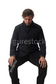 A mystery man, sitting on a bench with a gun – shot from mid level.