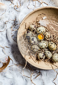 Quail eggs in a brown ceramic bowl