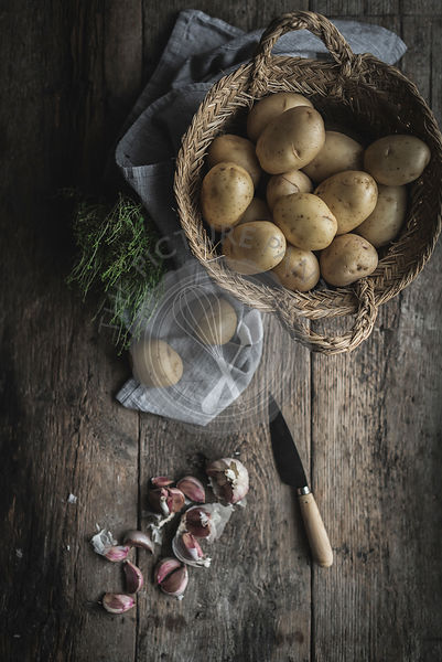 Potatoes and garlic cloves on a wooden table