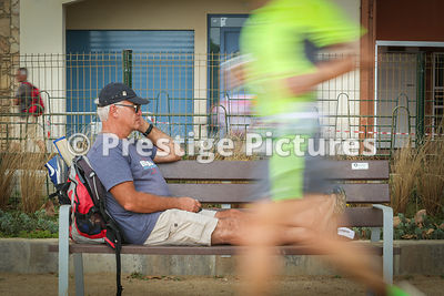 Stock photo - man resting on bench in the middle of a Triathlon