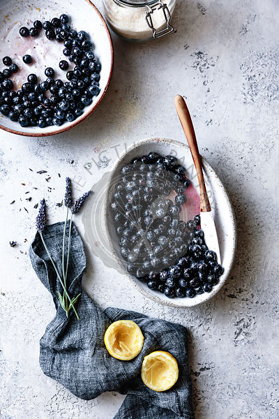 Blueberries in a ceramic dish with lemon and lavender.