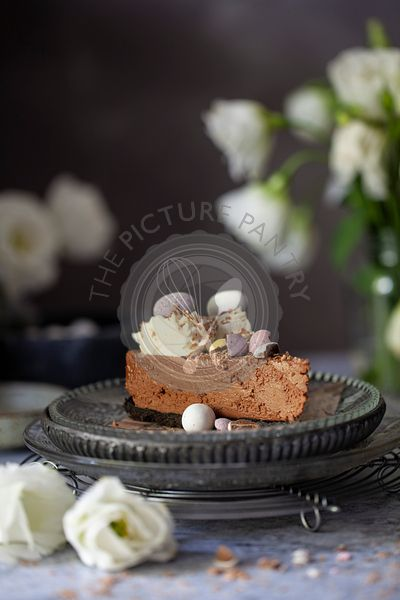 A slice of no-bake chocolate cheesecake decorated with whipped cream, chocolate flakes and candy Easter eggs