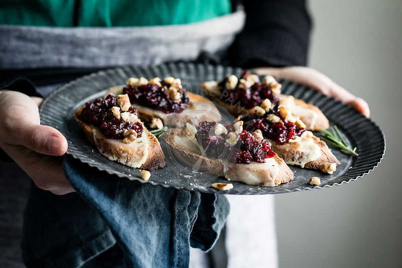 A woman holding a tray of cheese crostini with rosemary cranberry fig jam