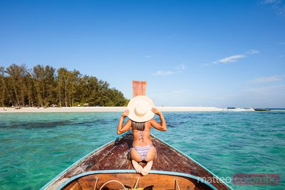 Woman holding straw hat on boat prow, Bamboo island, Thailand