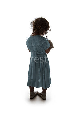 A semi-silhouette of a litle girl holding a teddy bear and looking away – shot from mid level.