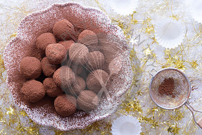 Homade chocolate truffles on a plate with a background of gold Christmas tinsel.