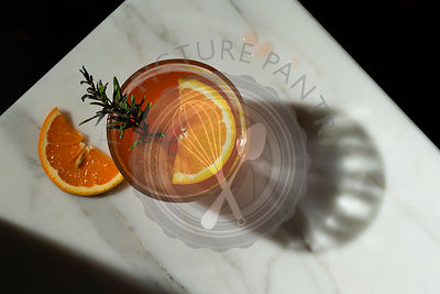 Negroni cocktail with a slice of orange and a smoking rosemary sprig garnish. The view is overhead looking down onto a marble...