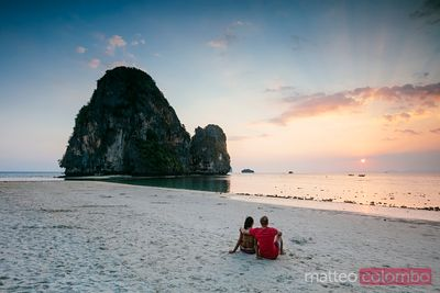 Tourist couple at Phra Nang beach at sunset, Railay, Thailand