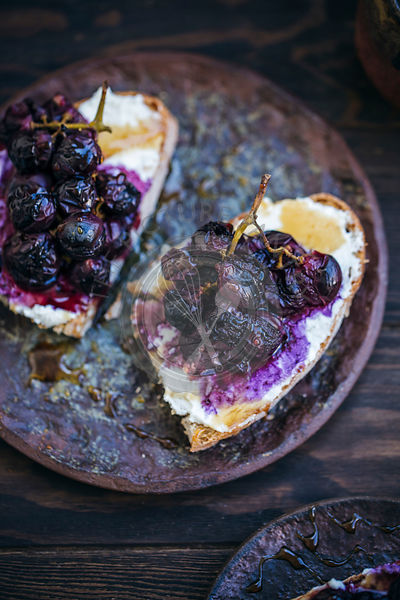 Toasted rye bread topped with ricotta cheese, roasted red grapes and honey