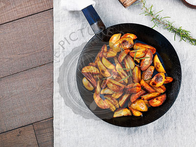 Roasted potato wedges with rosemary in a wrought iron pan on a tablecloth, top view