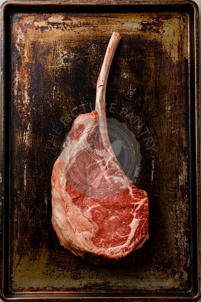 Raw fresh meat Tomahawk Steak on bone on dark background