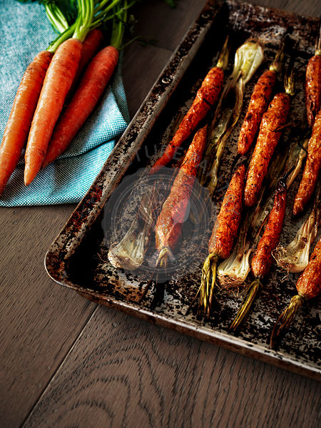 Roasted carrots and shallots on a tray