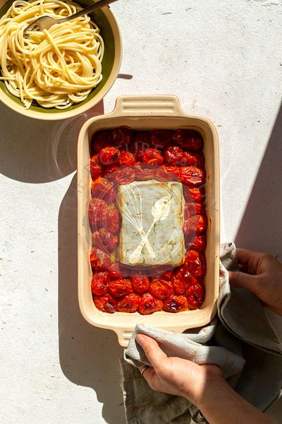 Baked feta cheese with tomatoes and pasta on a baking dish