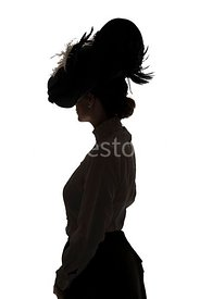 A Silhouette of an Edwardian woman in a big hat, standing and looking away – shot from eye-level.