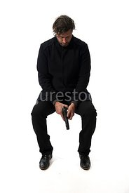 A mystery man, sitting on a bench with a gun – shot from eye level.