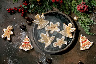 Christmas gingerbread cookies with icing ornate. Xmas decorations, dark background. Top view
