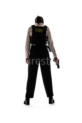 A tough woman FBI agent, in silhouette, holding a gun – shot from low level.