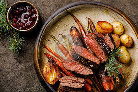 Grilled sliced Venison Steak with baked vegetables and berry sauce on dark background