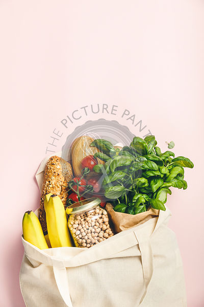 Flat-lay of healthy grocery shopping eco-friendly bag with fresh vegetables, fruit, bread, herbs and legumes over pink backgr...