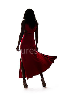 A silhouette, of a woman in a red dress – shot from low level.