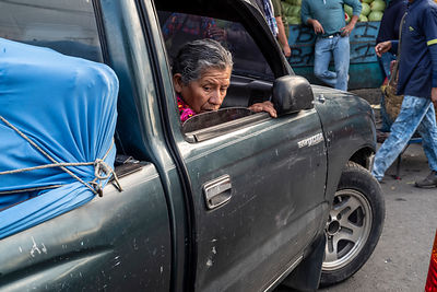 A woman looks out from a laden vehicle turning in the crowded Mercado Terminal