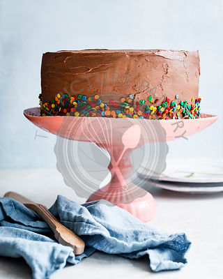Chocolate frosted celebration cake on a pink cake stand.